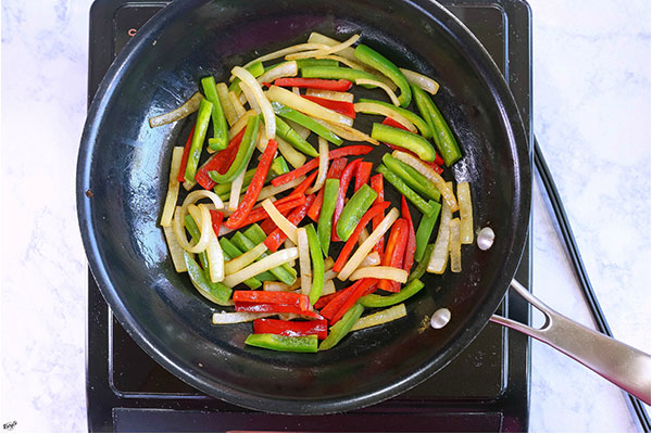 overhead process shot of veggies sauteeing in a black skillet