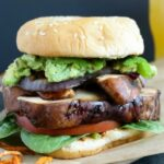 Loaded zesty portobello burger on parchment paper with a beer in the background