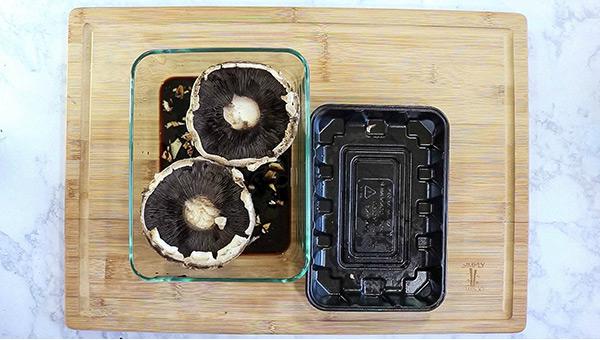 overhead process shot: portobello mushrooms in marinade in a glass container