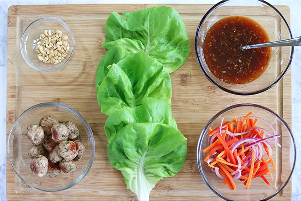 Overhead process shot: lettuce pieces, vegetables, meatballs, sauce, and crushed peanuts on a wooden board, ready to prepare