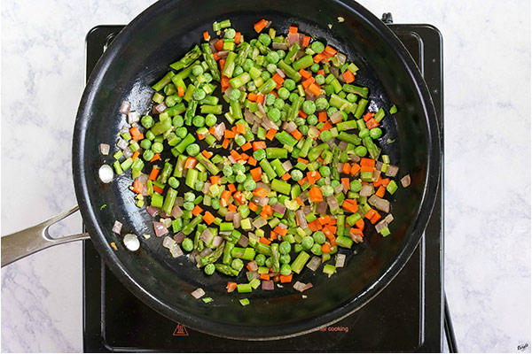 overhead process shot: all vegetables cooking in a black skillet