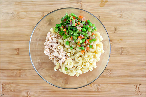 overhead process shot: pasta, tuna and vegetables in a glass bowl