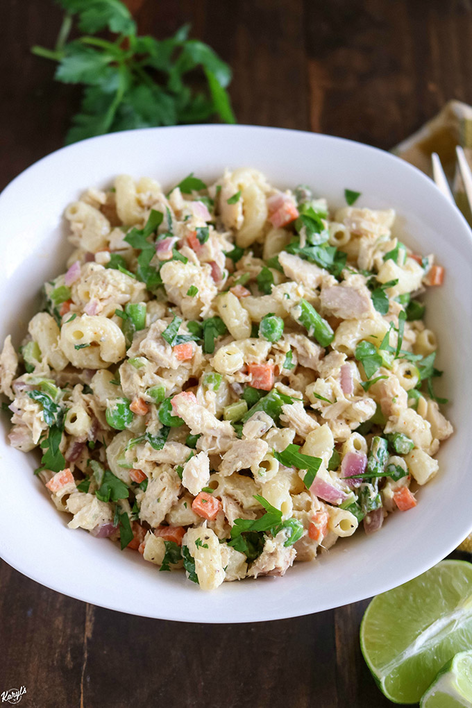 overhead angled shot of finished tuna pasta salad in a white bowl with parsley in the background