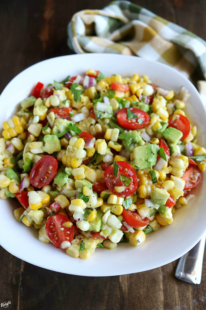 overhead angled shot of finished corn tomato avocado salad in a white bowl with a napkin on the side