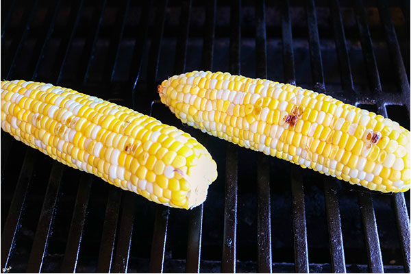 process shot: close up shot of corn cooking on the grill