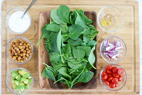 overhead process shot: salad ingredients in separate containers on a wooden board
