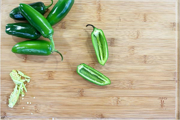 process shot: overhead shot of jalapenos with one jalapeno sliced and cored