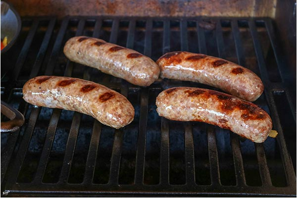 close up shot of brats cooking on the grill