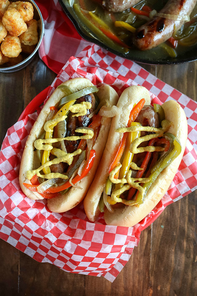overhead shot of 2 finished brats topped with mustard in a basket with a red and white paper