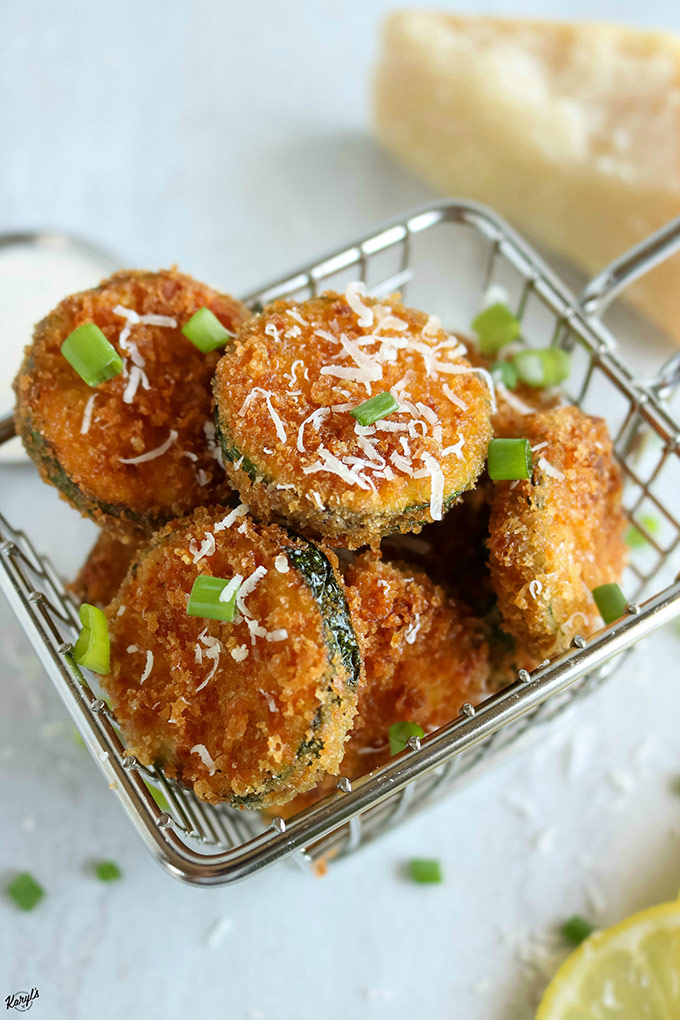 overhead shot of a stack of Panko Parmesan Zucchini Chips in a wire basket with a wedge of Parmesan on the side