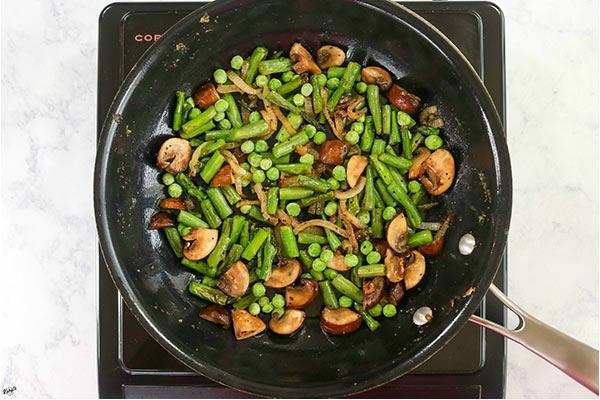 overhead process shot: vegetables cooking in a black skillet