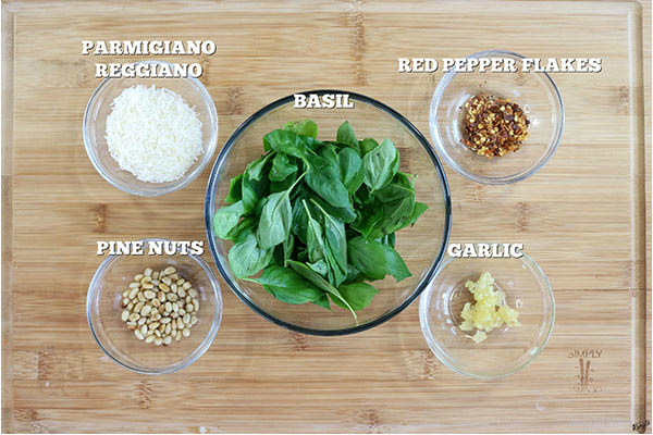 overhead process shot: pesto ingredients in separate bowls on a wooden board