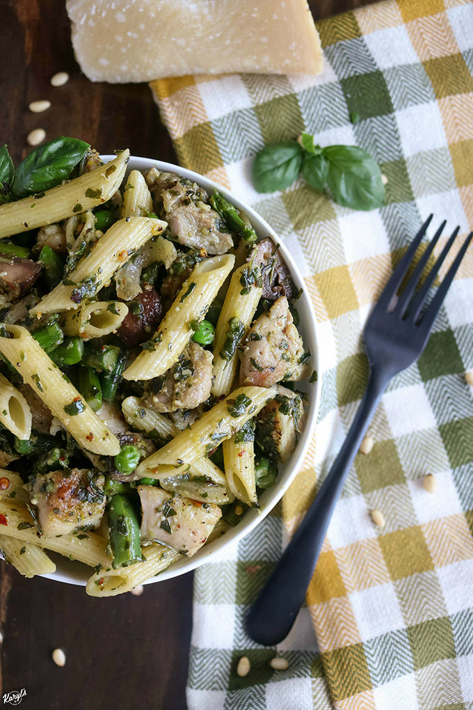 overhead shot of finished chicken penne pasta in a white bowl offset to the left with a fork and napkin on the side