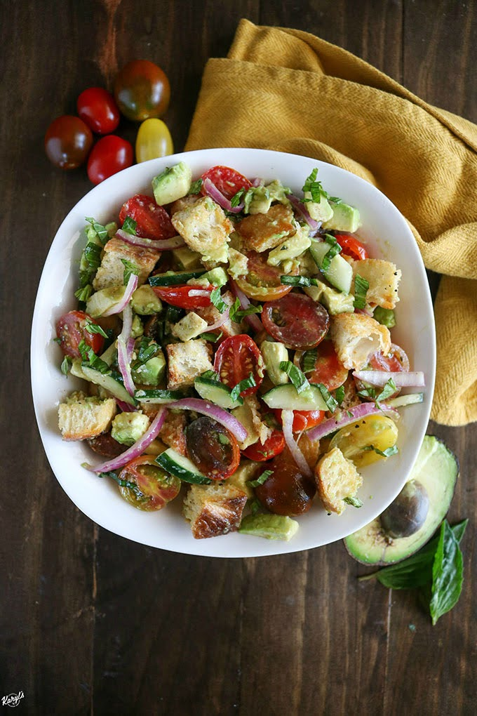 overhead shot of finished panzanella salad in a white bowl with avocado and tomatoes on the side