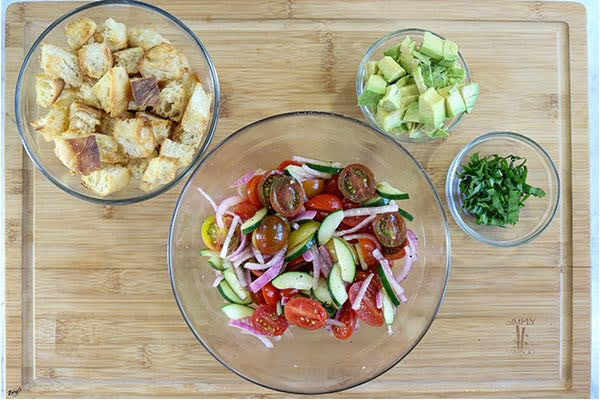 overhead process shot: large bowl of vegetables, plus smaller bowls of bread, avocado and basil
