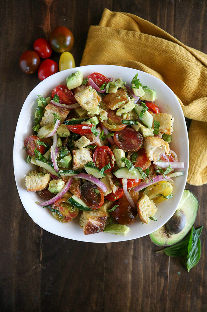 overhead shot of finished panzanella salad in a white bowl with a yellow napkin on the side