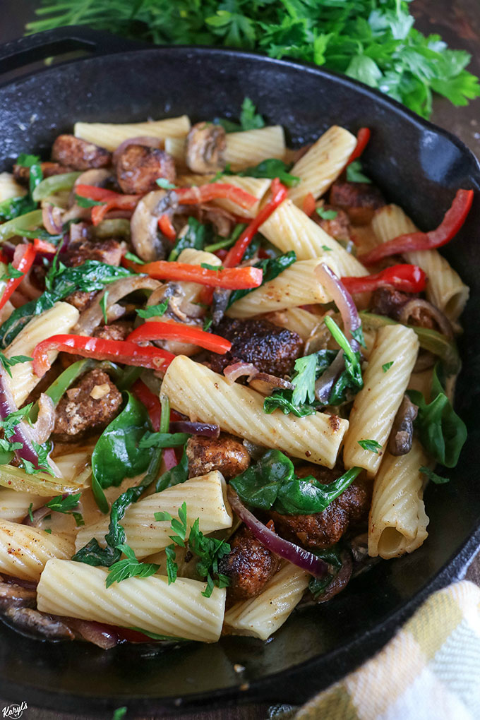 Close up angled shot of finished Cajun Chicken Vegetable Pasta in a black skillet with parsley in the background