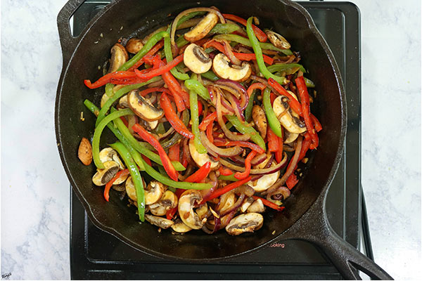 Overhead process shot: peppers, onions and mushrooms cooking in a cast iron skillet