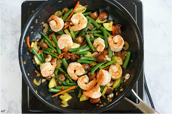 overhead process shot: vegetables and shrimp cooking in a black skillet