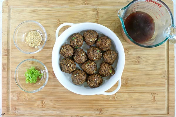 overhead process shot: baked meatballs in a white bowl, sauce in a measuring cup, plus sesame seeds and spring onions in small bowls
