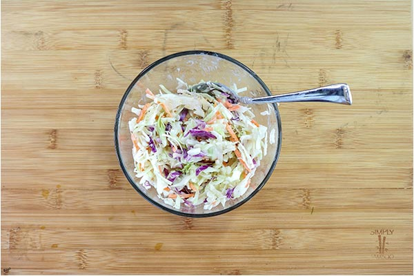 Overhead process shot: Coleslaw in a glass bowl