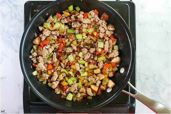 Overhead process shot: ground turkey added to the vegetables in the skillet.