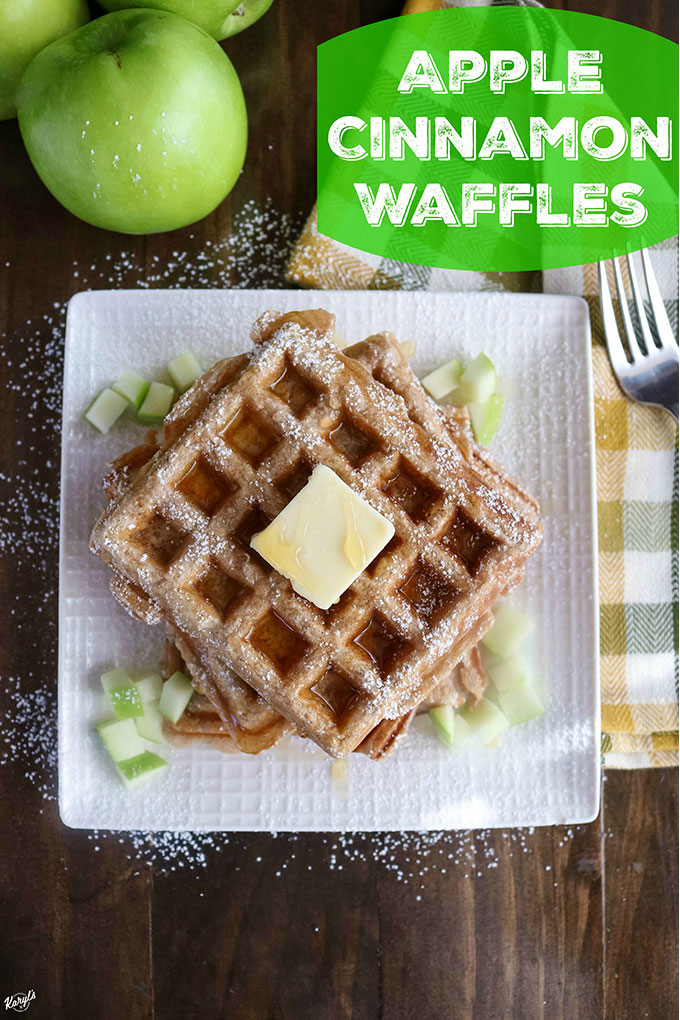 Overhead shot of finished Apple Cinnamon Waffles on a white plate with a couple of apples in the background