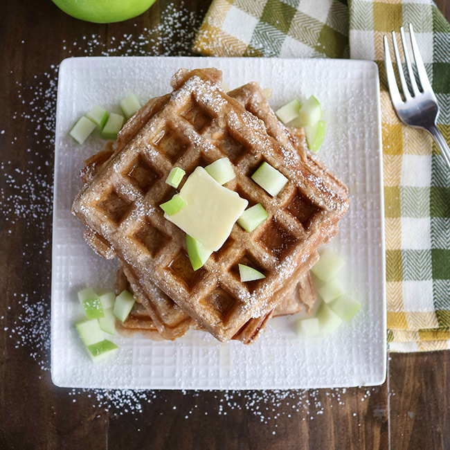 Overhead shot of a stack of finished Apple Cinnamon Waffles on a white plate, topped with diced apple