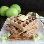 Close up shot of a stack of Apple Cinnamon Waffles on a white plate with 3 apples in the background