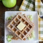 overhead shot of stack of Apple Cinnamon Waffles with a pat of butter on top on a white plate