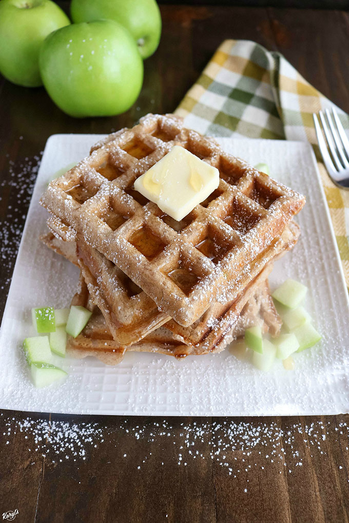 Angled shot of finished Apple Cinnamon Waffles on a white plate with diced apples on the plate