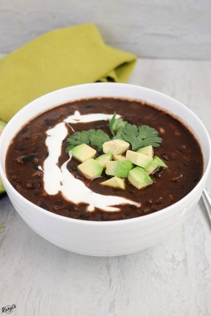 Close up shot of black bean soup in a white bowl