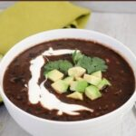 angled close up shot of a bowl of black bean soup garnished with avocado and sour cream