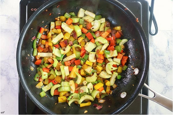 Overhead process shot: peppers, onion and bok choy stems cooking in a black skillet