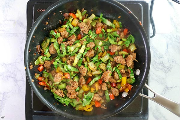 Overhead process shot: vegetables and Italian sausage cooking in a black skillet