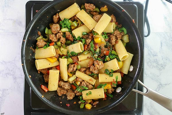 Overhead process shot: all Italian Sausage Bell Pepper Pasta ingredients in a black skillet