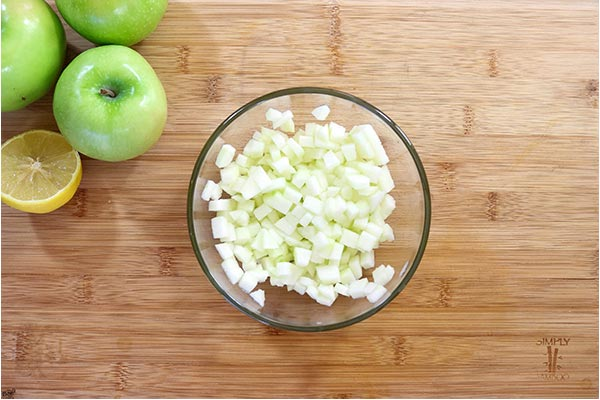 Overhead process shot: diced apples in a glass bowl on a wooden board
