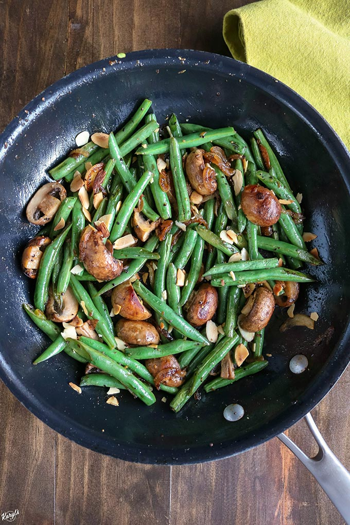 Overhead shot of finished Green Bean Mushroom Saute in a black skillet with a green napkin on the side