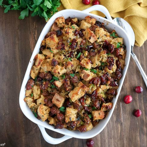 overhead shot of finished Sausage Sage Cranberry Stuffing in a white baking dish
