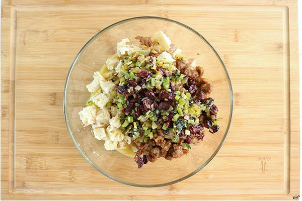 Overhead process shot: all stuffing ingredients combined in a large glass bowl