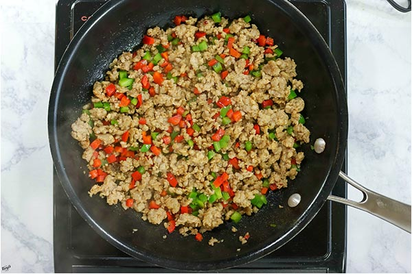 overhead process shot: sausage, seasonings and peppers cooking in a black skillet