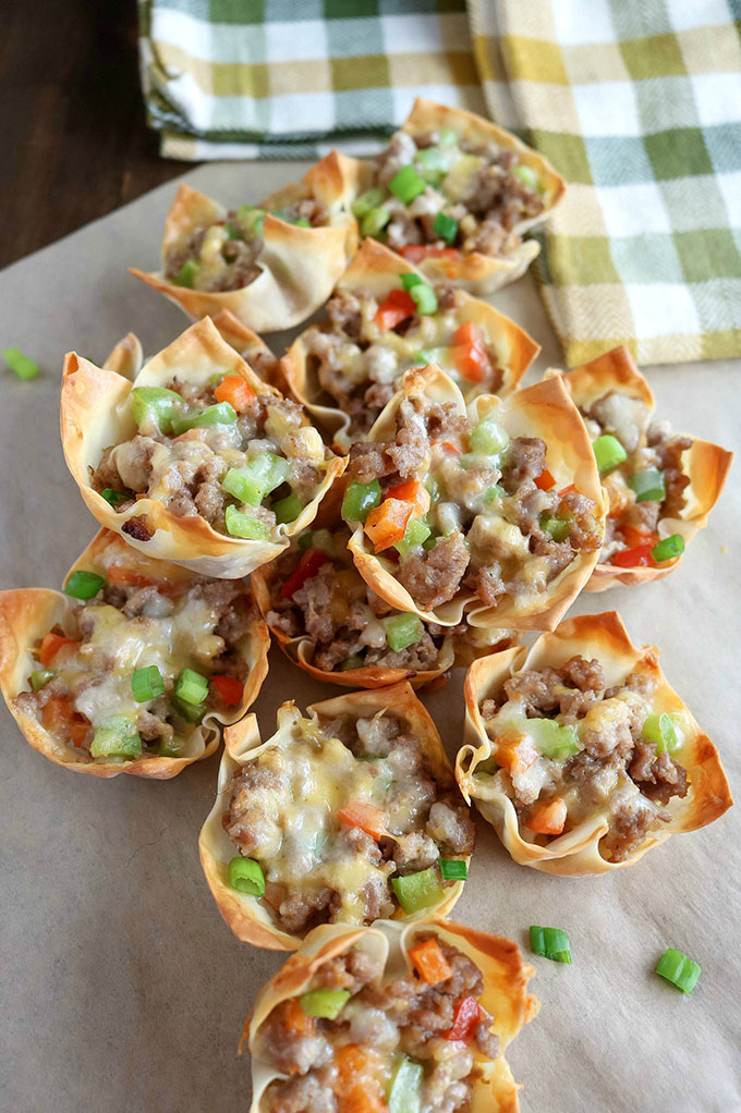pile of Sausage Pepper Wonton Cups on paper with a napkin in the background