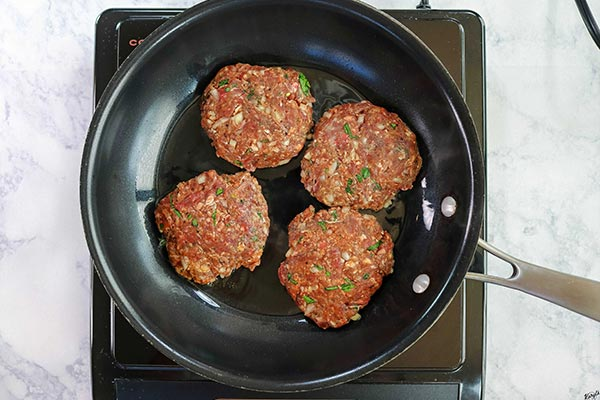 Overhead process shot: venison patties cooking in a black skillet