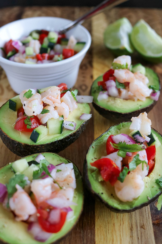 close up shot of 4 avocados filled with ceviche, plus a bowl of ceviche in the background